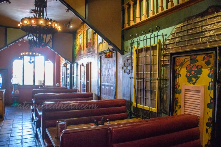 Interior of Pizza Show. Maroon upholstered booths line the walls that have been painted to look like small Italian buildings with bricks, windows, and doors.