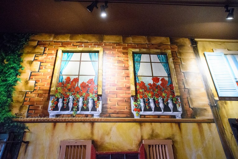 Interior of Pizza Show - Mural of a faux window, with a flower bed jutting from the bottom of the painted window.