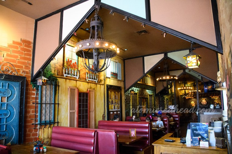Interior of Pizza Show, with murals that make the place feel like a small Italian village, faux doors and faux shutters line the wall, iron chandeliers hang from the celing.