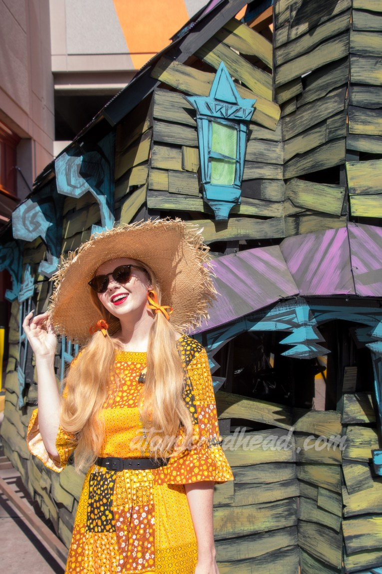 Myself standing in front of a green, purple, and blue haunted house float, wearing a patchwork print dress of orange, yellow, black and white, as a large straw hat