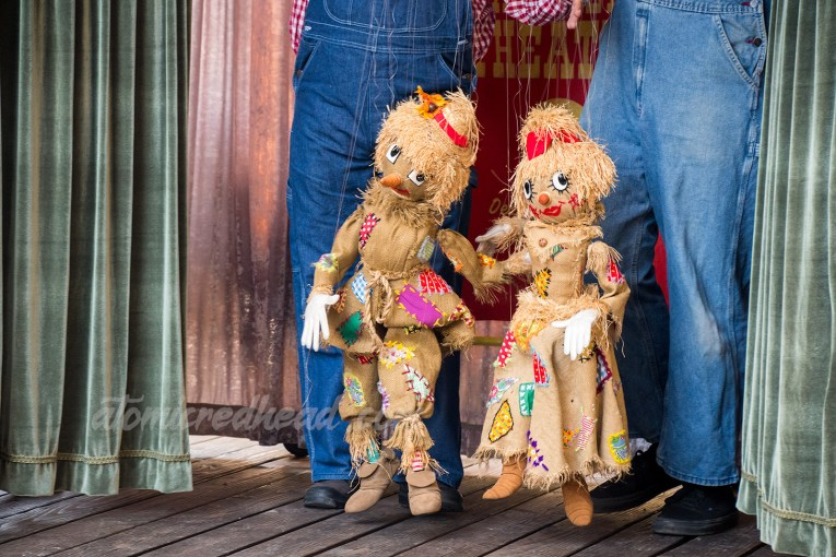A pair of scarecrow marionettes made of burlap with patches.
