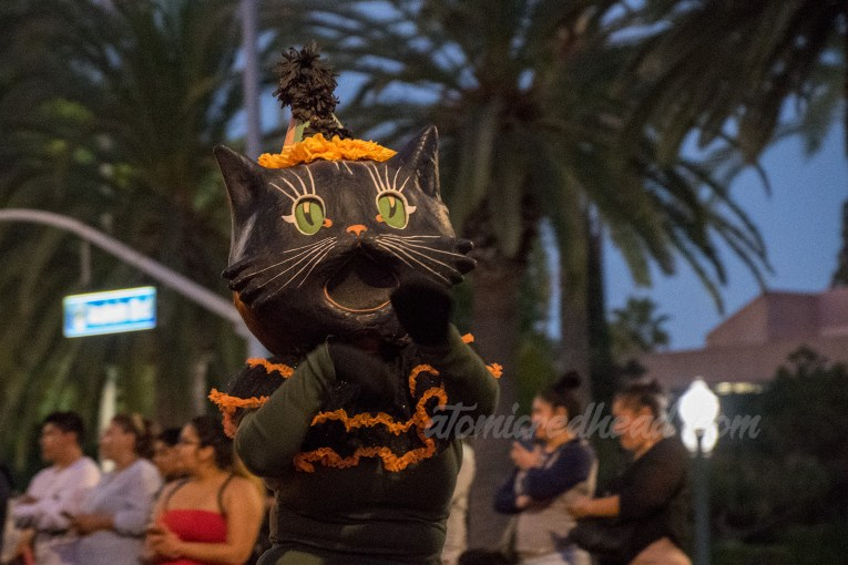 A parade performer wears a large black cat mask.