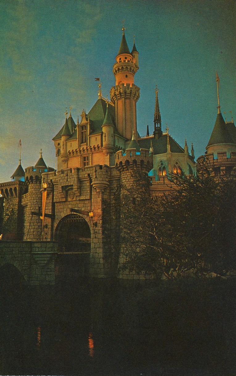 Sleeping Beauty's Castle at dusk, appearing a dusty pinky-yellow with teal rooftops.