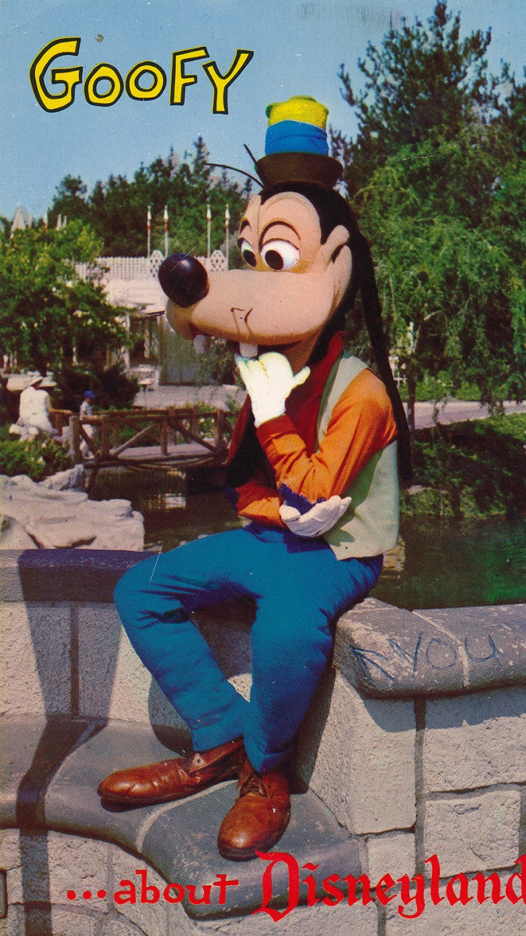 """Goofy sits on a wall near the castle, his hand in his mouth, text reads """"Goofy for Disneyland"""""""