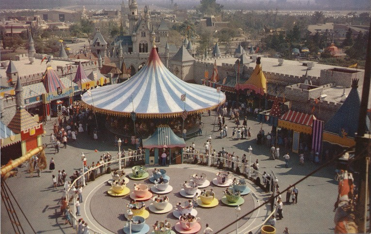 A view from above. Spinning brightly colored tea cups near a blue and white stripe canopy that is the carousel, the Castle just behind.