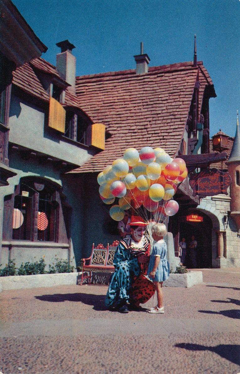 A clown holding balloons chats with a young girl in front of Merlin's Magic Shop.