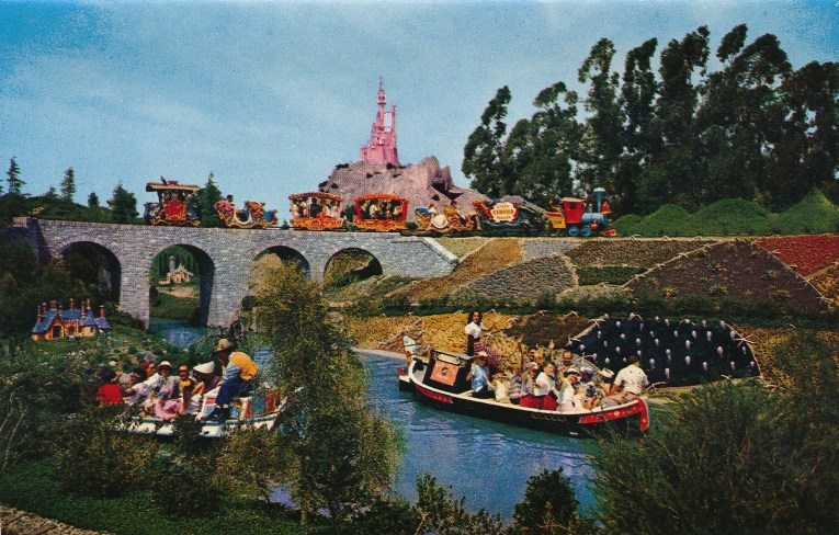 Boats from Storybookland glide through the water as the look at miniature versions of the homes from characters from Disney films. Casey Jr. chugs along in the background.