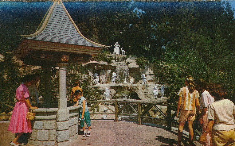 Snow White's Wishing Well stands on the left, with a waterfall featuring statues of Snow White and her seven dwarf friends. Guests walk by, a few look into the well.