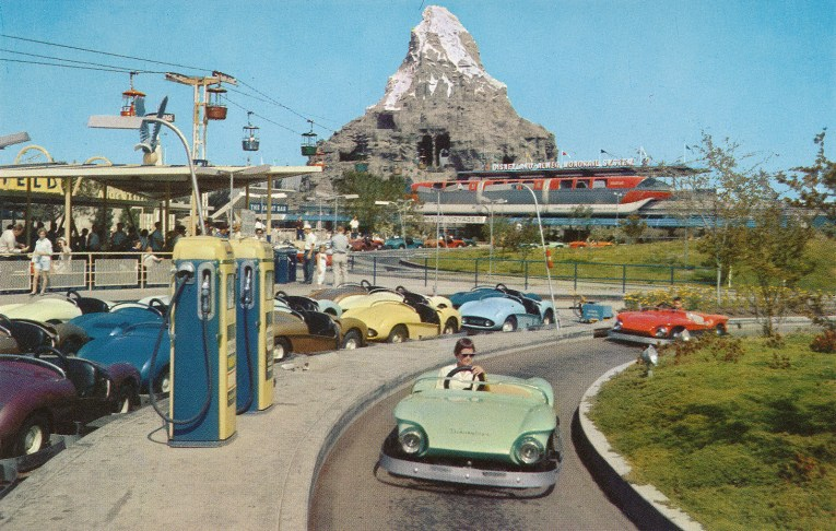 Guests drive the Autopia cars while the Matterhorn looms in the distance.
