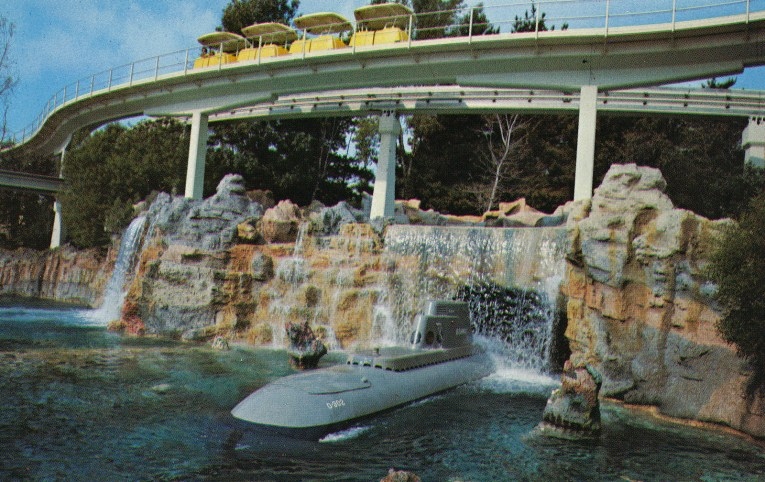 A grey submarine emerges from a waterfall, while yellow PeopleMover cars glide on a track high above.