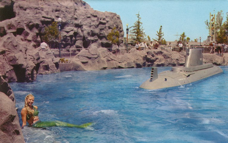 A grey sub moves through the water, a mermaid sits atop a rock on the left.