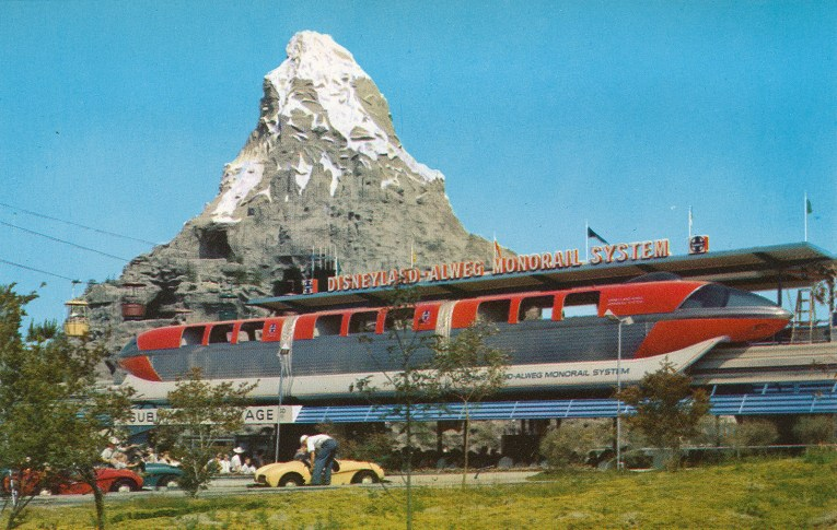 A red monorail is docked at the boarding area in Tomorrowland, the Matterhorn stands tall and snowcapped in the background.