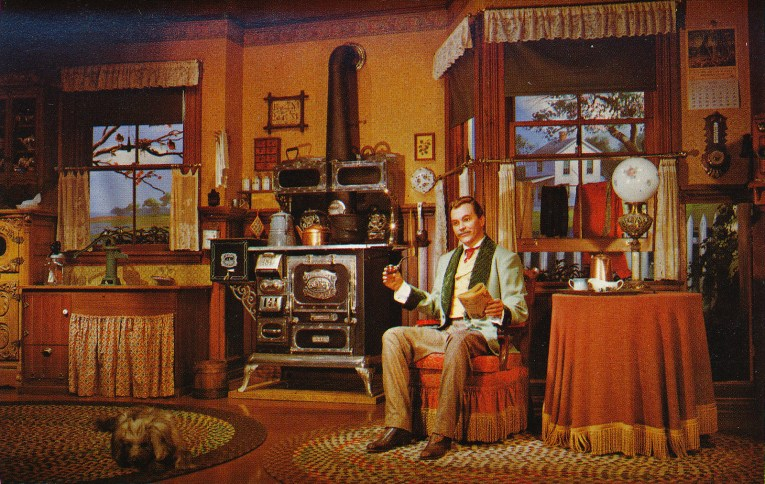 Inside the Carousel of Progress, the world of 1890, a man with a pipe talks to guests, a wood burning stove in the back, an oil lamp on the table.