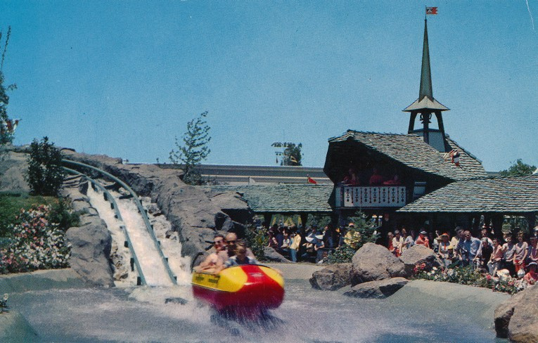 A red and yellow bobsled lands in water as it comes down the tracks of the Matterhorn.