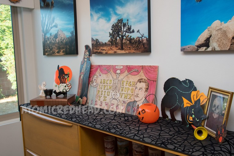 A top a secretary sits a wood burned spirit board featuring Vincent Price, a skeleton, and Carol Ohmart. Next to it is a cardboard skeleton dressed as a pirate, another cardboard piece of a black cat on top of a skull. Also next to the spirit board is a small plastic jackolantern, a cardboard black cat, and an image of a woman looking in a vanity, but it also looks like a skull.
