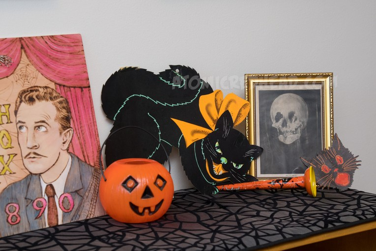 Close-up of the small jackolantern, black cat, which has an orange bow, image of a woman sitting at a vanity, but also looks like a skull, a metal horn with the image of a witch on it, and a small black cat head.