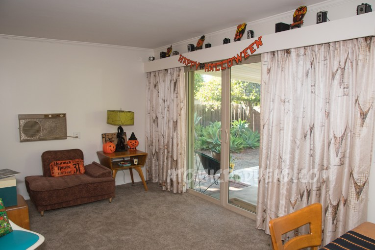 "To the right curtains hang in front of a sliding glass door, above the sliding glass door a banner reads ""Happy Halloween"" in orange, edged in black. Above it are vintage cameras, along with cardboard Halloween decorations of a witch, owl, cat, and pumpkin. On the left a 50s chair sits next to a table, a pillow that looks like a ticket stub for a Haunted House sits on it. On the table a plastic jackolantern trick-or-treat bucket and a pumpkin with a witch hat on it."