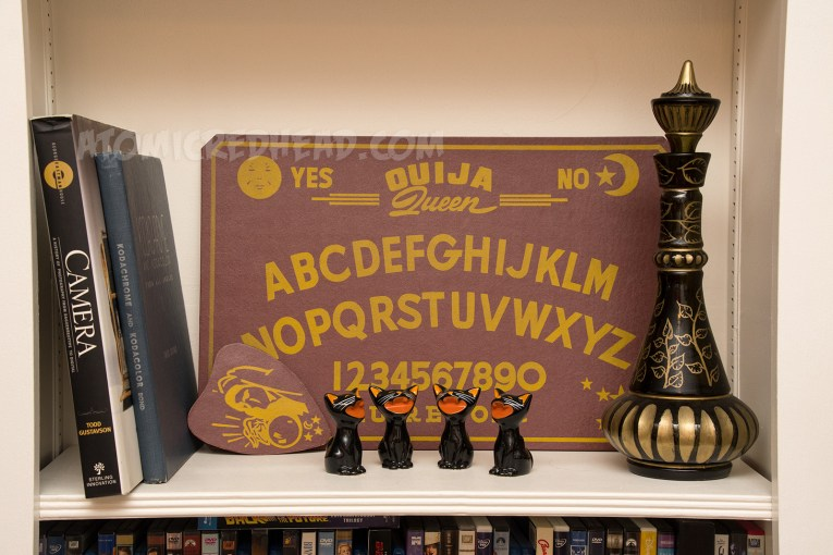 "A maroon spirit board reading ""Ouija Queen"" and a series of ceramic black cats sit."