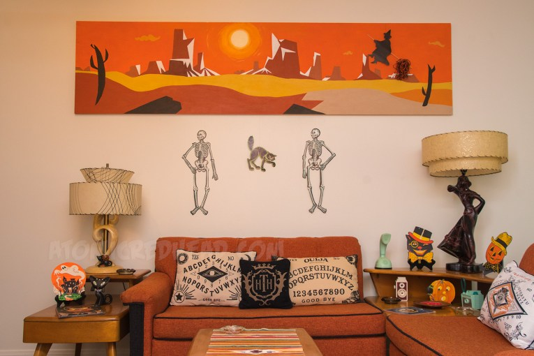 Below a painting of a desert scene hang two skeletons and a black cat above an orange and black couch. On the couch spirit board pillows sit.