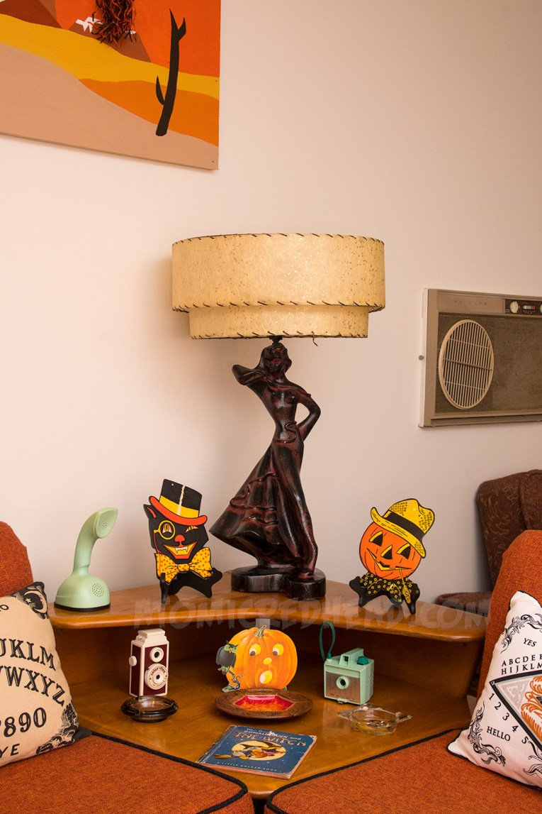 On a table sit cardboard Halloween decorations of a black cat in a top hat and bowtie, and a pumpkin in a straw hat and bandana, a piece of straw juts from his mouth. Below them a small jackolantern appears scared of an owl.