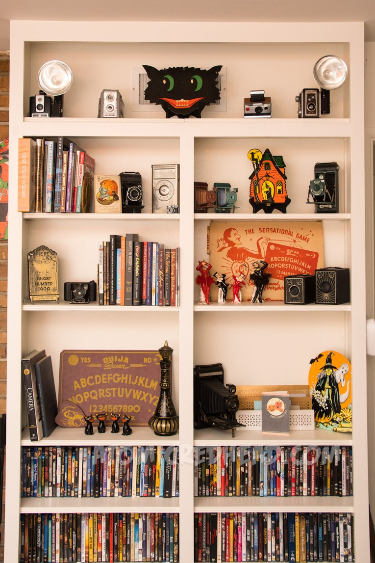 A bookshelf full of books and DVDs, but also a spirit board, a series of ceramic black cats and ceramic devil girls, and a cardboard house with a witch in the doorway, and on the top vintage cameras and a cardboard black cat head.