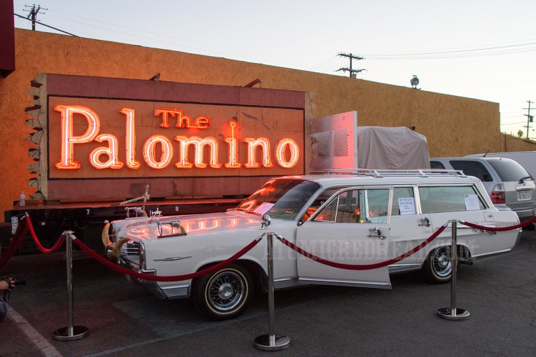 One of Nudie's cars, which features bull horns on the grill, a guns atop the front fenders. In the background sits the red neon glowing sign of The Palomino.