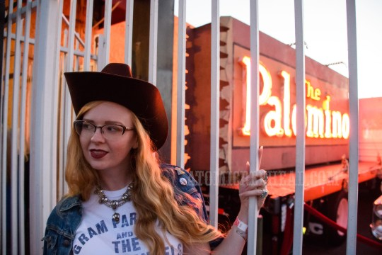 """Myself standing in front of the Palomino sign, wearing a blue jean jacket, white t-shirt reading """"Gram Parsons and the Fallen Angels"""" and a dark brown cowboy hat."""