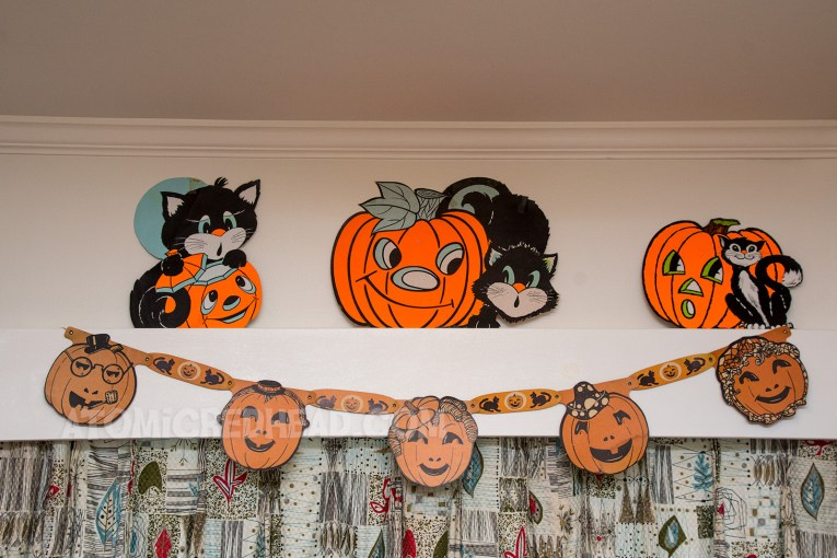 Three black cats with jack-o-lanterns, sit on top of a valance, while a banner made of jointed jack-o-lanterns hangs below.