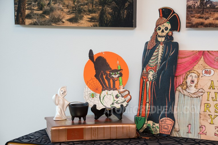 A flat decoration with an image of a black cat standing on a skull sits on top of a black plate stand.