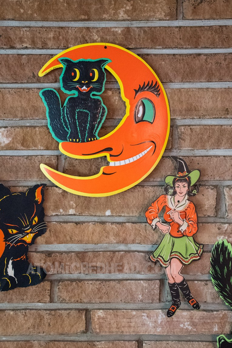 A cat sitting in the moon, and a witch dancing hanging against a brick wall.