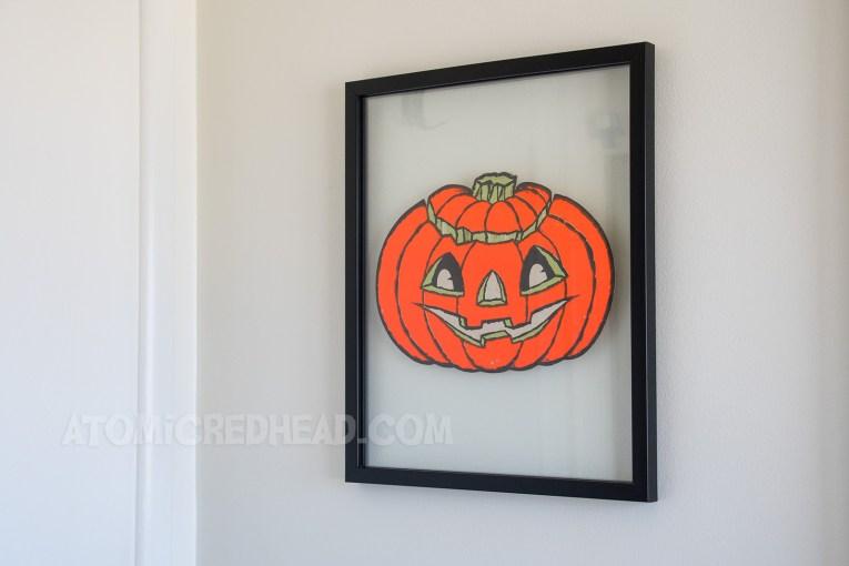 A flat paper jack-o-lantern in a frame.