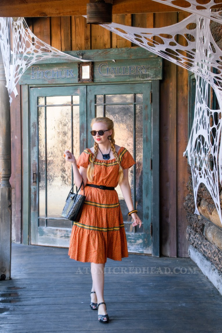 Myself walking along side old western buildings, wearing an orange dress with a small yellow and green floral print, and yellow and green rick-rack along the neckline and skirt, carrying a black tooled leather purse, also wearing black tooled leather shoes, and a plastic black cat necklace.