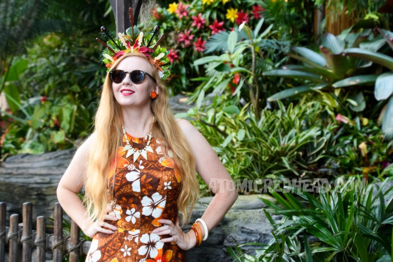 Myself wearing a brown, orange, and white floral maxi dress, and a crown made of orange and yellow flowers and swizzle sticks from Trader Sam's, featuring tiny tikis.