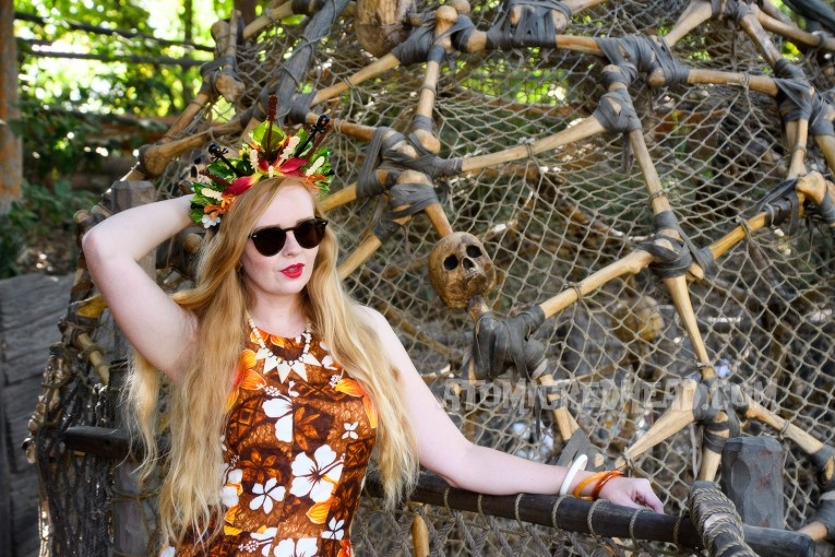 Myself, leaning against a round cage made of skulls and bones, wearing a brown, orange, and white floral maxi dress, and a crown made of orange and yellow flowers and swizzle sticks from Trader Sam's, featuring tiny tikis.