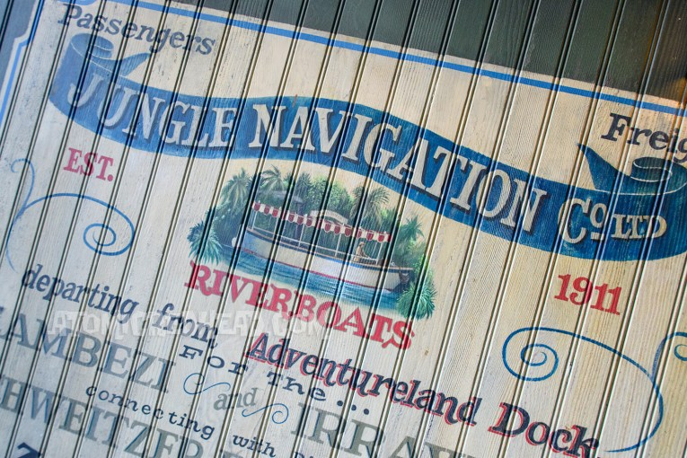 """Mural of the Jungle Cruise, featuring an image of one of the boats gliding through the water. Reads """"Jungle Navigation Company Riverboats. Departing from the Adventureland Dock"""""""