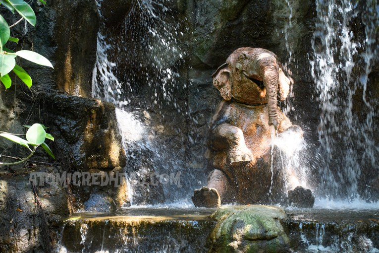 An elephant bathes in a waterfall.