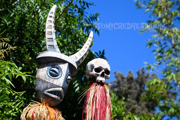 Tiki mask with horns and a skull sit upon posts.