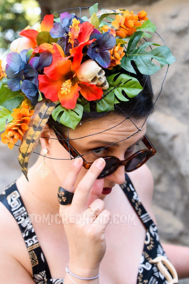 Mandy, her fascinator made with a metal spiderweb, and covered in colorful flowers and leaves and small skulls. She looks at the camera, tilting her sunglasses down.