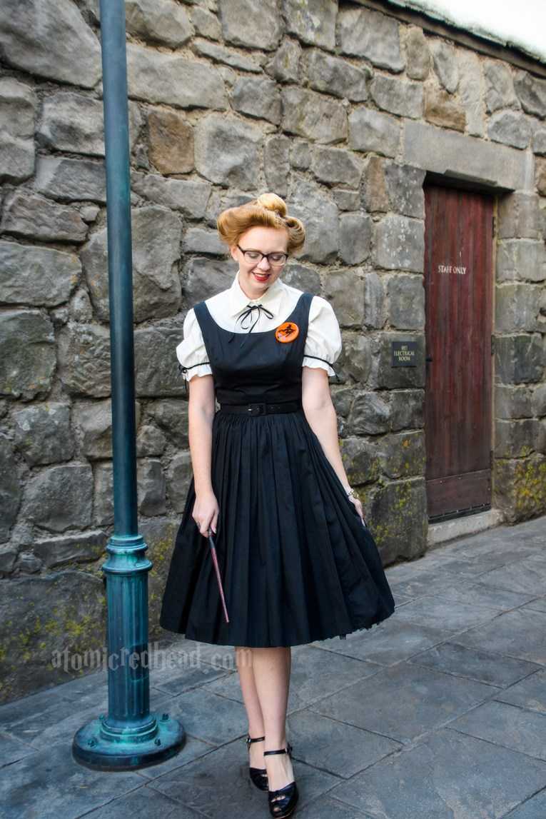 Wondering the stone alleyways of Hogsmeade, wearing a white blouse under a black dress. A brooch of a witch on a broom worn on my left.
