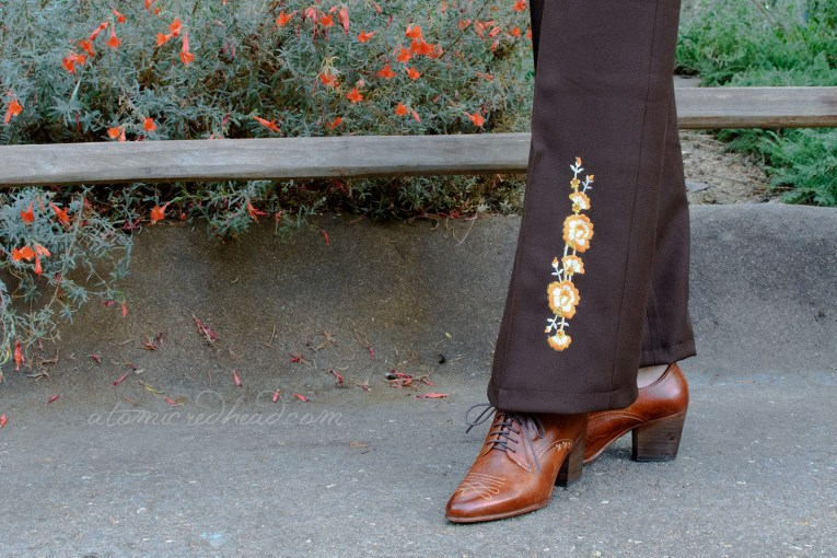 Close-up of the bottom part of my pants, which features orange, white, and gold embroidered flowers dotted with orange rhinestones.