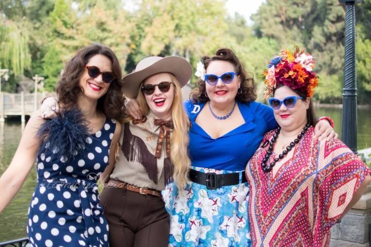 From left to right, my friend Nikki, wearing a navy dress with large white polka dots, myself, my friend Dor, wearing a bright blue top with a skirt of blue and white with airplanes, and my friend Kaitlyn, wearing a red, white, and navy blue patterned dress and a large floral crown.