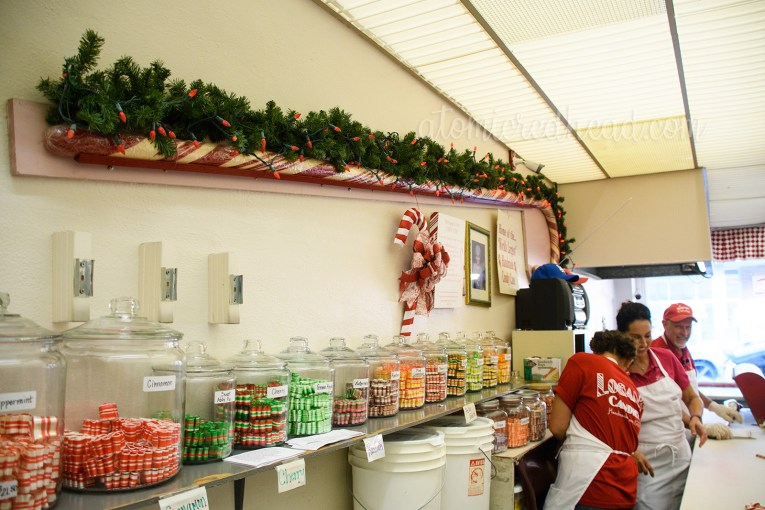 "The ""World's Largest"" hand-made candy cane hangs on the wall behind the candy counter."