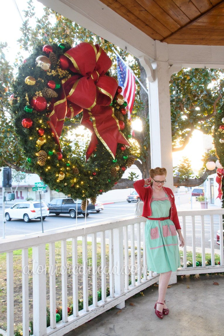 Myself standing in a covered white bandstand wearing a mint green dress with red and white stripe pockets, a red sweater, a Christmas tree brooch, white purse, and red shoes. A large Christmas wreath hangs in the background.