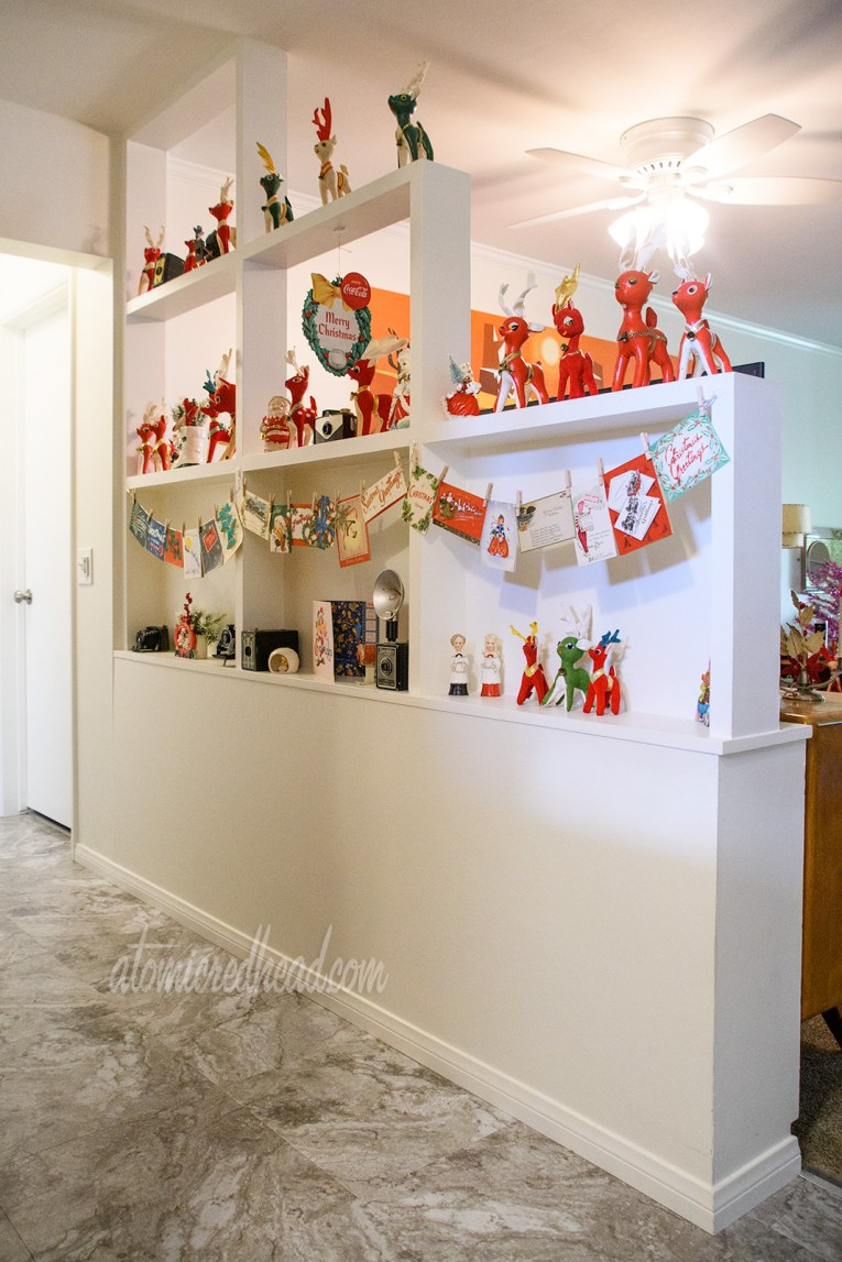 Small, red reindeer line shelves, and vintage Christmas cards hang like clothing on a line from a ribbon.