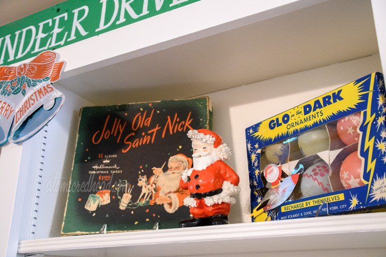 "A vintage card box features Santa painting toys, next to it stands a ceramic Santa, and next to it is a box of ""Glo in the Dark"" ornaments, the box is blue and feature bright yellow stars."