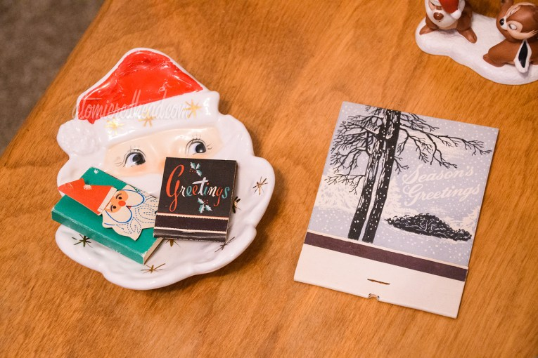 "A Santa head dish holds two matchbooks, one of a Santa head, the other black reading ""Greetings"" in red, green, and white script with holly."