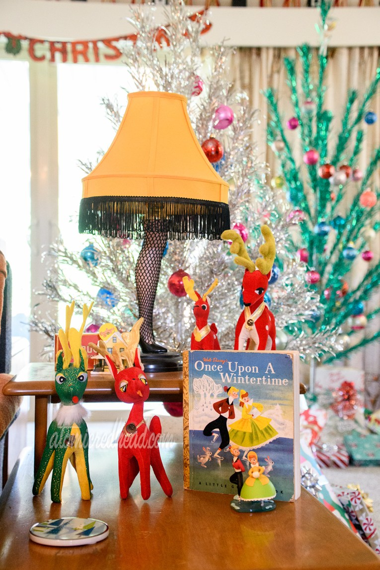 "The iconic Leg Lamp from A Christmas Story sits on an end table, with various small, stuffed reindeer, and a book of ""Once Upon a Wintertime"" which features a boy and girl ice skating."