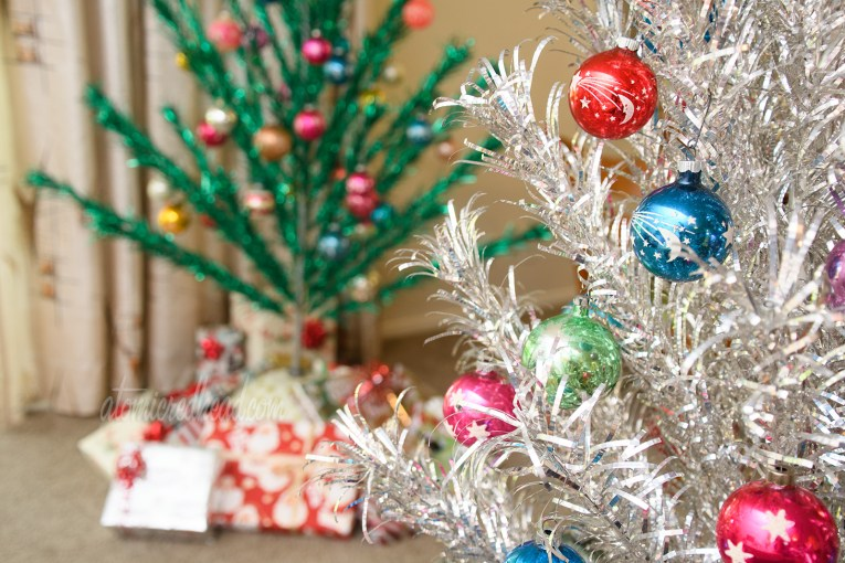In the foreground a silver aluminum tree features multi-colored glass ball ornaments with stars, moons, and planets on them. In the background a green aluminum tree with similar ornaments.