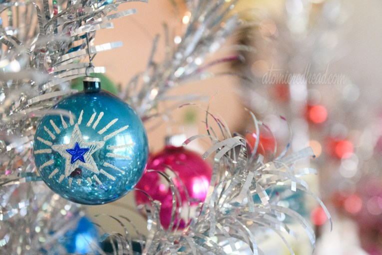 A close up of a blue ornament with a star on it hanging on a silver aluminum tree.