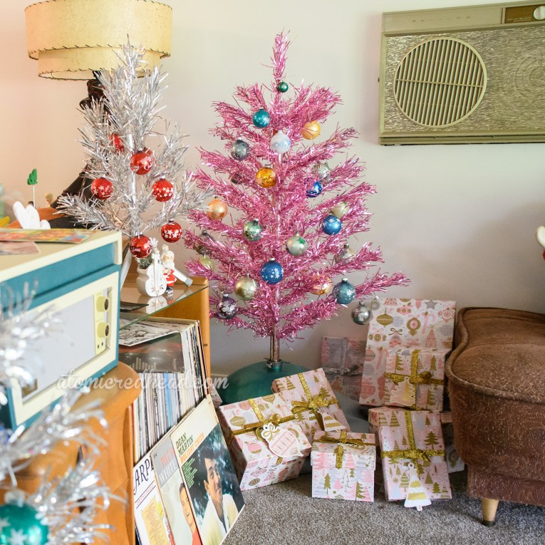 A pile of presents sit under a pink aluminum tree that has been elevated slightly off the ground.